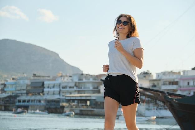 Спортивная зрелая женщина, бегающая трусцой на морской набережной