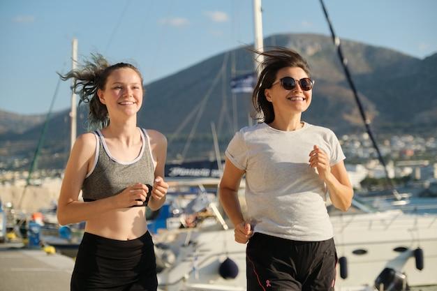 Мама и дочка бегают вместе на набережной