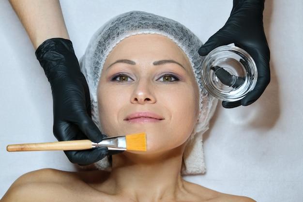 ビューティーサロンでの化粧品の年齢の手順で成熟した女性のクローズアップ顔