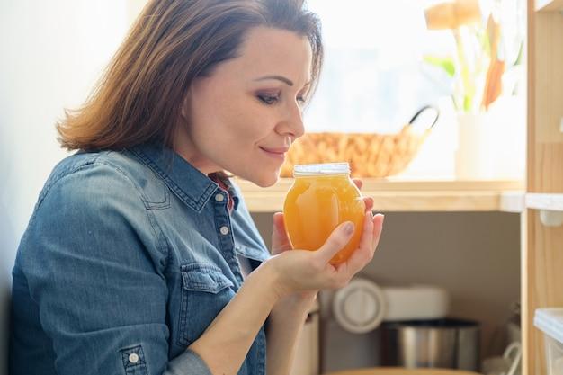 Женщина с банкой золотого органического свежего меда на кухне