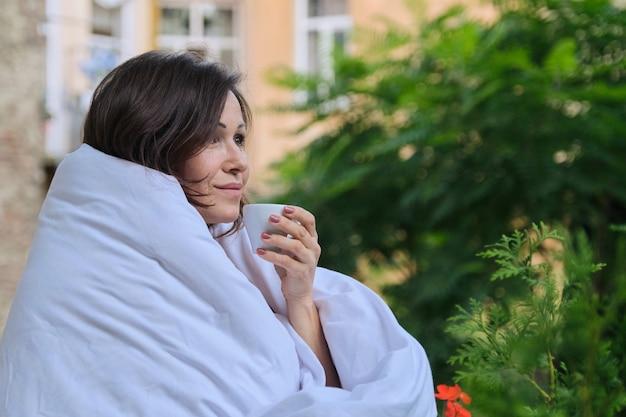Улыбка счастливая женщина средних лет с чашкой кофе, одетая в одеяло