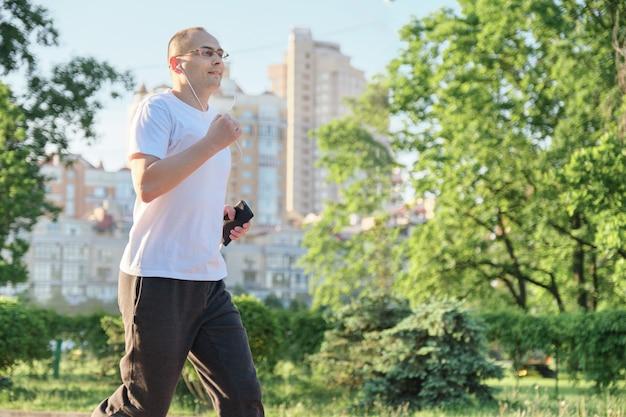 公園で走っている中年男性、アクティブな健康的なライフスタイル