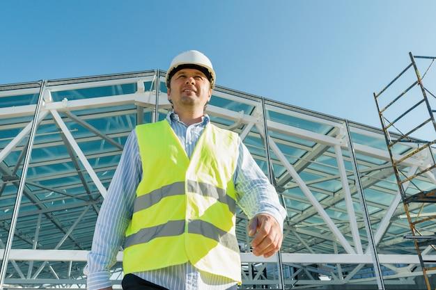 Мужской строитель идет вперед по крыше строительной площадки