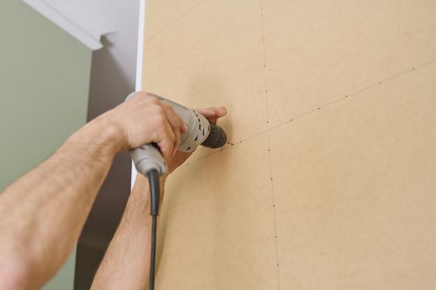 プロのツールでキッチンを組み立てる家具をやっているハンドワーカーのクローズアップ