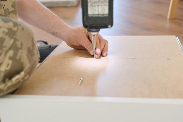 プロのツールと家具の詳細を持つ労働者の手のクローズアップ