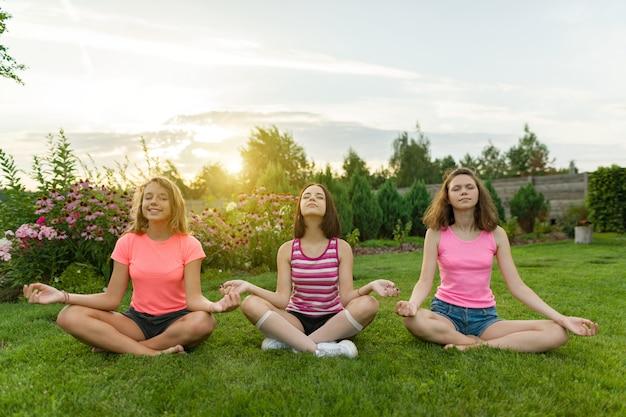 Группа девушек-подростков занимается йогой, медитирует