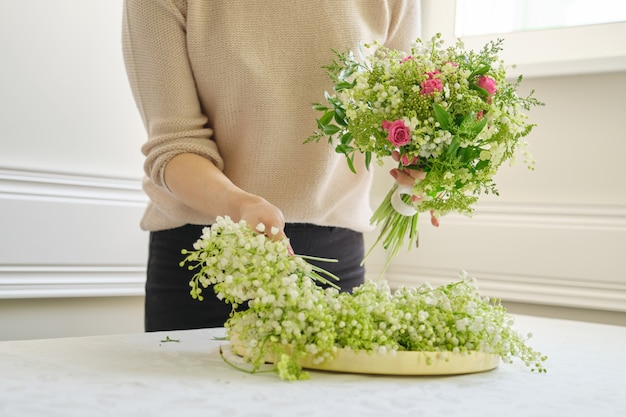 ブーケを作るテーブルに別の花を持つ女性花屋