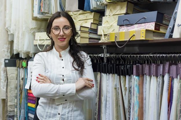 インテリア生地店で組んだ腕を持つ女性オーナー
