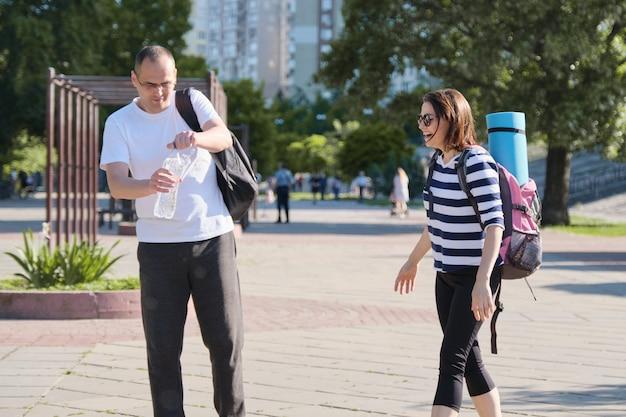 成熟した笑みを浮かべて男とボトルから飲料水を話している都市公園を歩いている女性