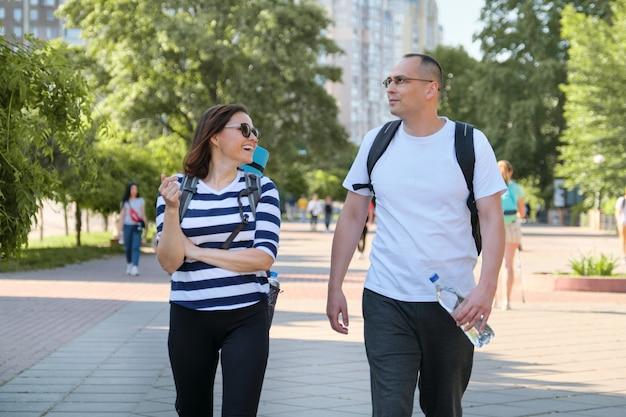 ウォーキングや公園で話しているスポーツウェアの中年夫婦