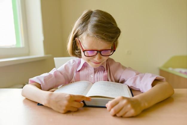 Маленькая девочка студент сидит за столом с книгой.