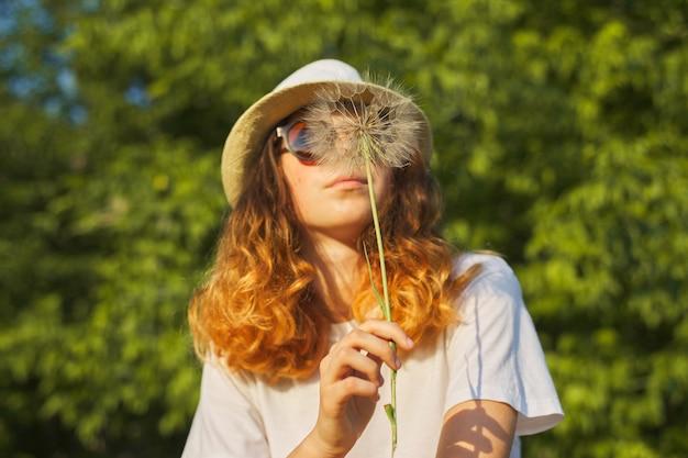 Летний открытый портрет романтичной девочки-подростка в шляпе с большим пушистым одуванчиком