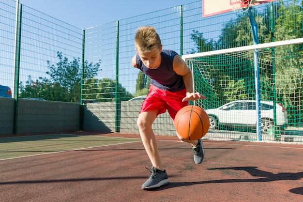 Мальчик подросток играет в баскетбол в городской баскетбольной площадке