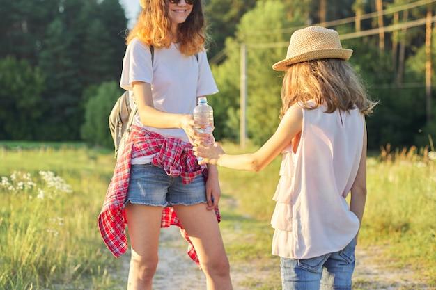 Дети двух девочек сестер с бутылкой воды в жаркий летний день на природе