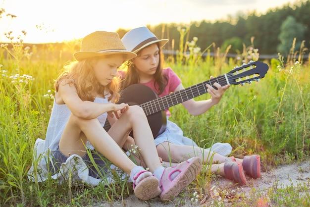 Дети сидят на природе с классической гитарой