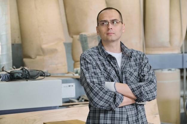 Портрет мужского работника в промышленном производстве. уверенный в себе человек со сложенными руками.