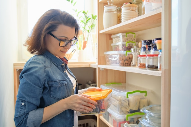 食物と一緒に木製の棚の近くのキッチンで自宅の女性