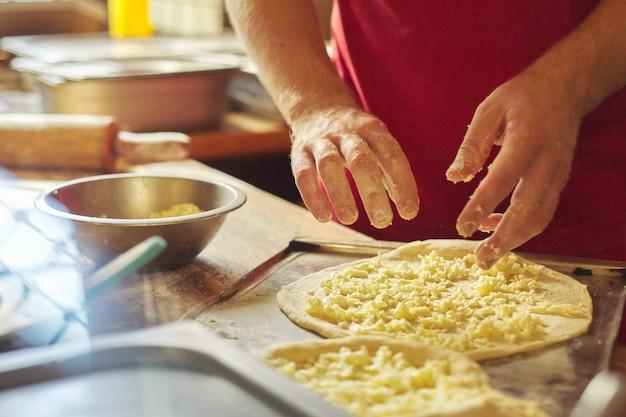Макро руки мужчины пекарь готовит традиционную грузинскую кухню хачапури