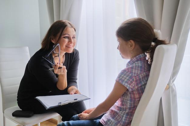 女の子に話している女性ソーシャルワーカー。児童心理学、メンタルヘルス
