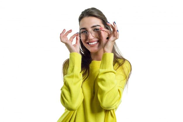 Молодая женщина в очках желтой одежде на белом