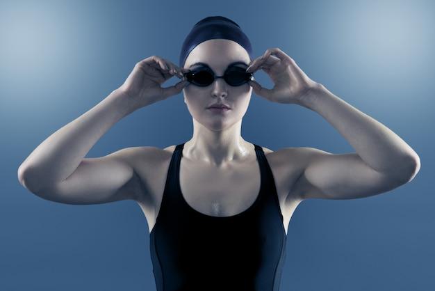Студийный портрет женщины-пловца с купальными очками