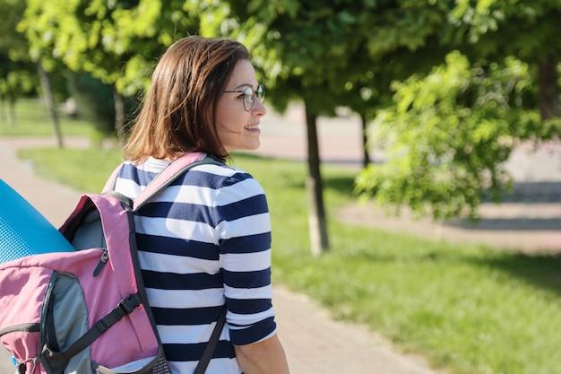 中年の女性が公園の道を屋外で歩く