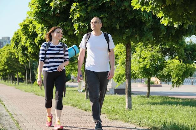 Говорят мужчина и женщина средних лет, пара гуляет по парковой дороге