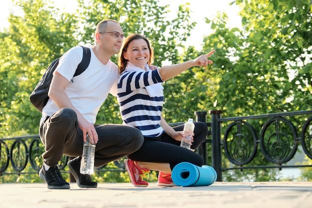 Счастливые улыбающиеся пожилая пара, сидя в парке, говорить отдыхает после занятий спортом