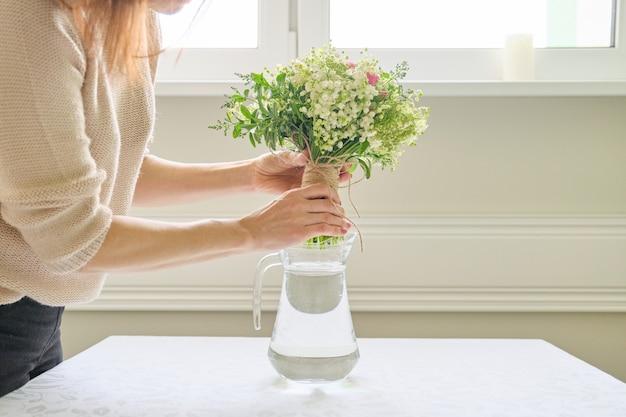 新鮮な春の花の花束、女性の花束を持って、テーブルの上に花瓶に配置