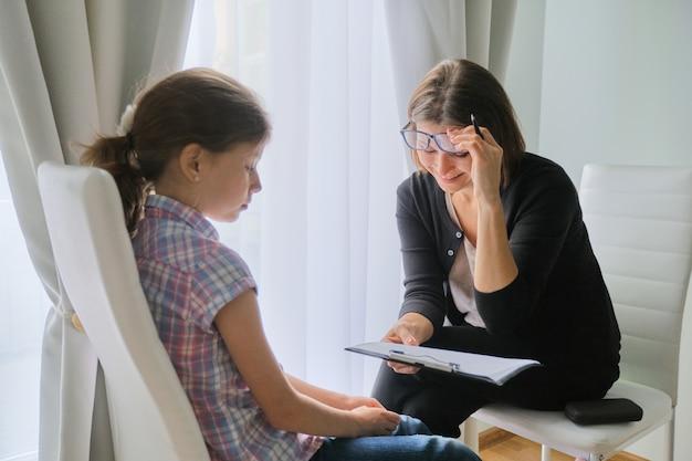 窓の近くのオフィスで話している女の子と女性の心理療法士