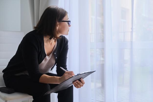 窓の外を見てクリップボードと成熟したビジネス女性