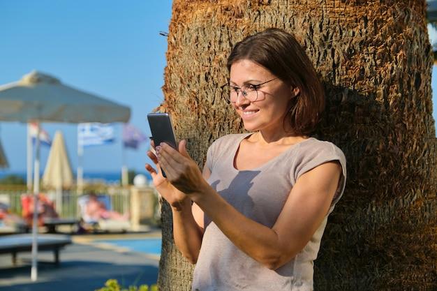 Женщина стоит возле пальмы в курортном спа-отеле в солнечный летний день