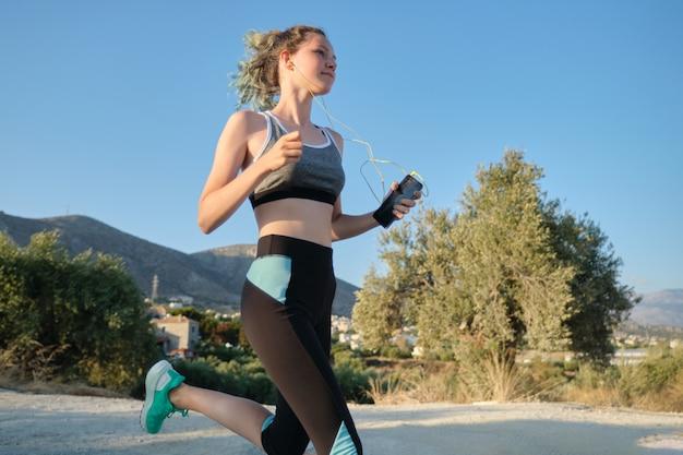 Бегущая молодая девушка-подросток в фитнесе одевает наушники со смартфоном