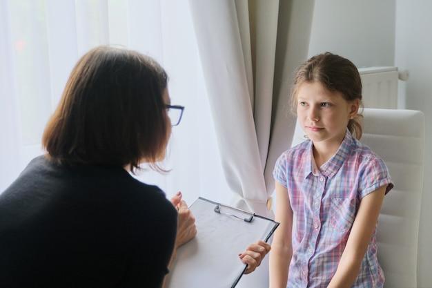 Женщина психолог работника разговаривает с девочкой в офисе