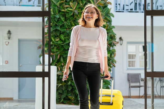 スーツケースをホテルのインテリアで成熟したビジネス女性