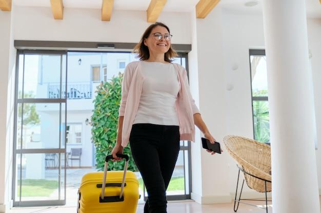 ホテルのロビーのインテリアにスーツケースを持つ女性ゲスト観光客。