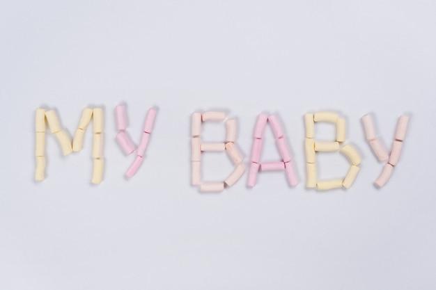 私の赤ちゃんという言葉は、白い壁にパステルマシュマロによって書かれています。