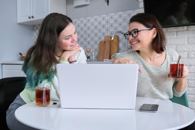 Родитель и подросток сидя дома на кухне и глядя на экран ноутбука