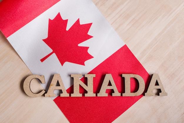 カナダの国旗、木製の抽象的な文字、木製の背景の単語カナダ