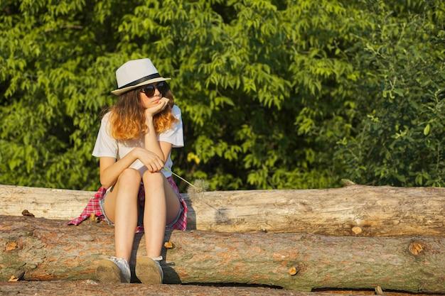 深刻な顔をして待っている自然の中でログに座っている十代の少女