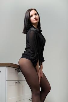 黒のナイロンパンストブラウスで美しい若い女性のポーズ