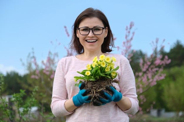庭の手に月見草の花を手袋で女性の春の肖像画