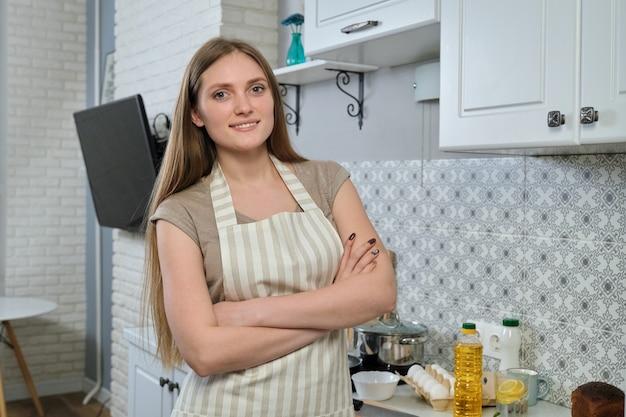 Молодая женщина в фартук со скрещенными руками, дома на кухне