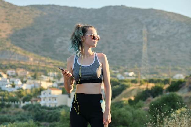Красивая фитнес бегун девушка с помощью смартфона и наушников