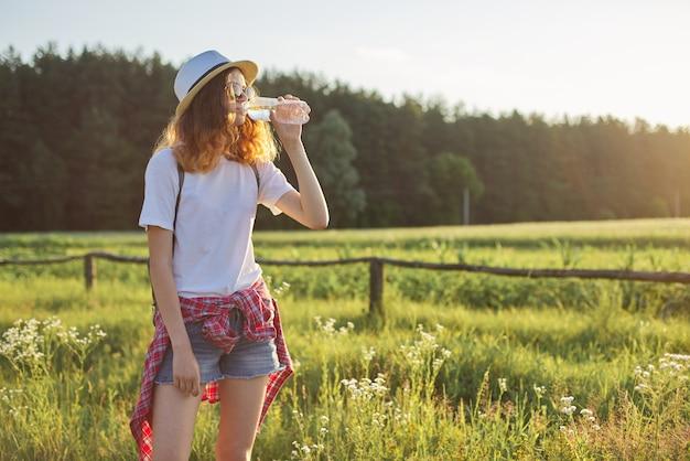 若い女の子はボトルから水を飲む