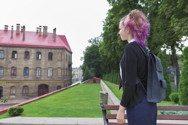 学校の制服を着たバックパックと屋外のティーンエイジャーの女の子学生