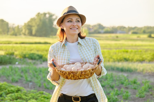 Деревенский портрет зрелой женщины с корзиной яиц на лугу