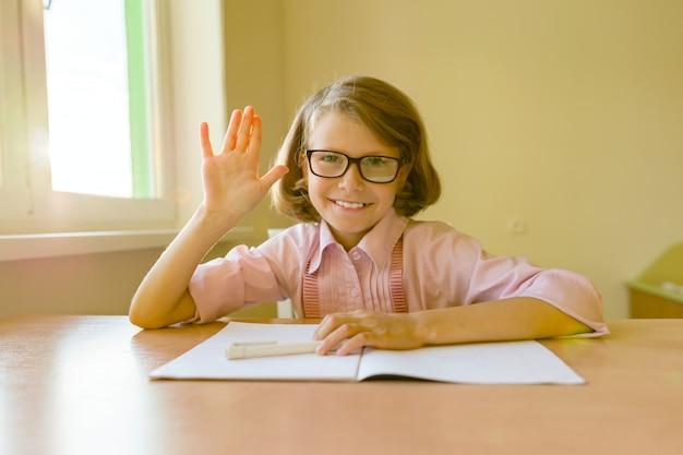 メガネの小さな学生は机に座っています。