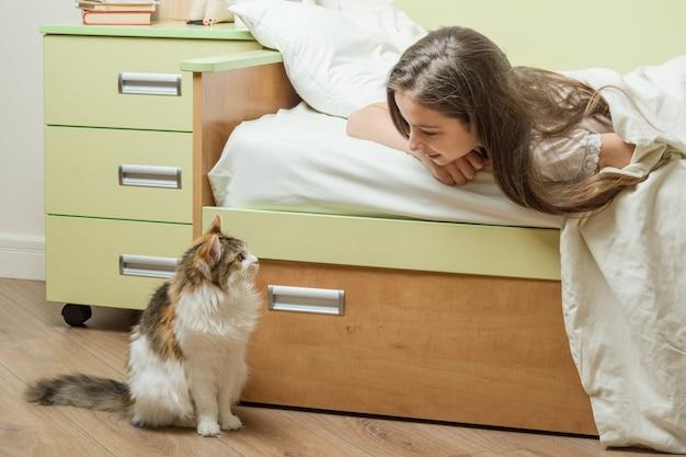 Кошка сидит возле кровати с ребенком