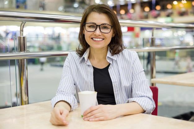 Среднего возраста женщина за столом с чашкой кофе